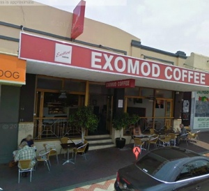 "A photograph of a coffee shop ""Exomod Coffee"". The entrance to the coffee shop has stairs."